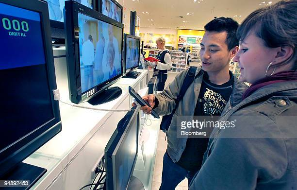 Steffi Neumann and Binh Vuduc shop for flat screen televisions at the Galeria Kaufhof department store in Berlin, Germany, on Tuesday, Feb. 26, 2008....