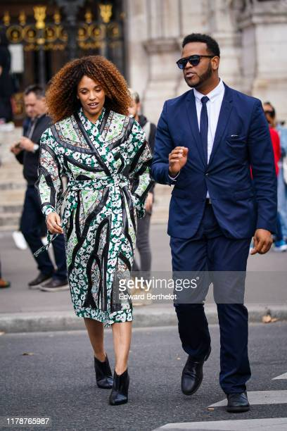 Stefi Celma wears a green and white patched floral print wrap dress with black crocodile pattern inserts black pointy heeled ankleboots outside...