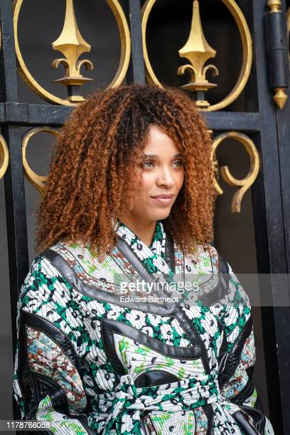 Stefi Celma wears a green and white patched floral print wrap dress with black crocodile pattern inserts outside Stella McCartney during Paris...