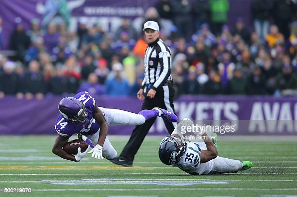 Stefon Diggs of the Minnesota Vikings gets tripped up by DeShawn Shead of the Seattle Seahawks while Referee Terry McAulay watches in the second...