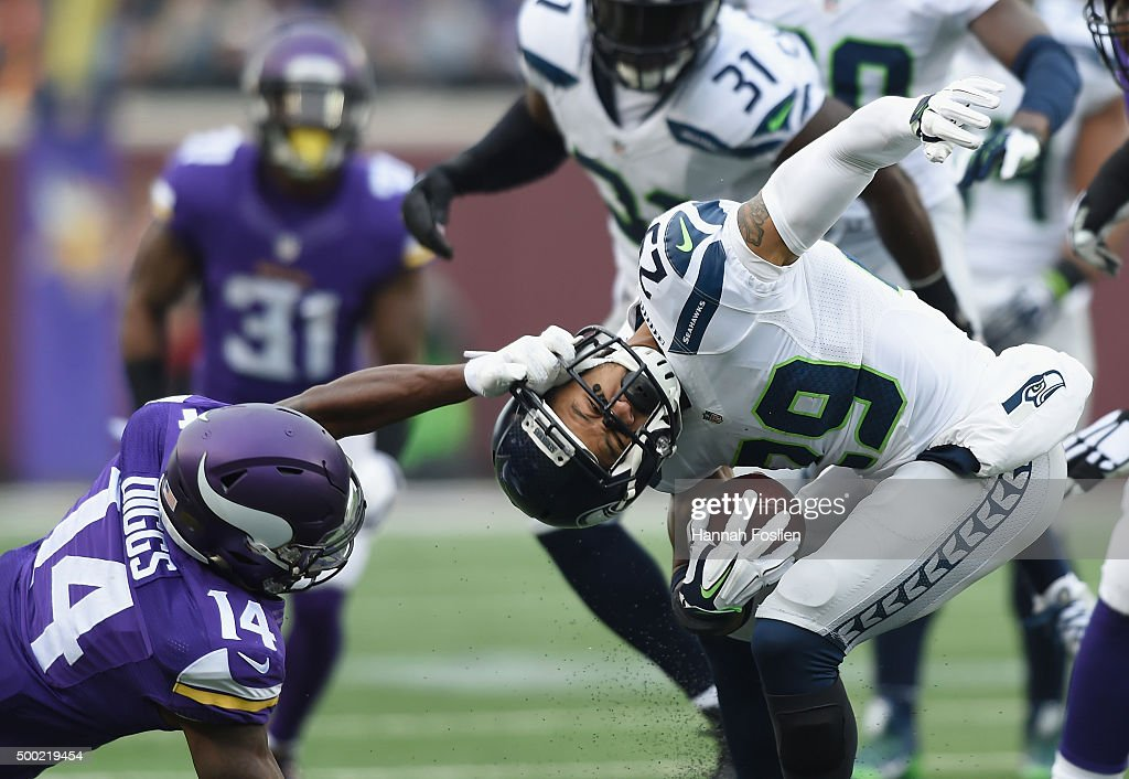 Stefon Diggs #14 of the Minnesota Vikings grabs the face-mask of Earl Thomas #29 of the Seattle Seahawks after an interception by Thomas during the second quarter of the game on December 6, 2015 at TCF Bank Stadium in Minneapolis, Minnesota.