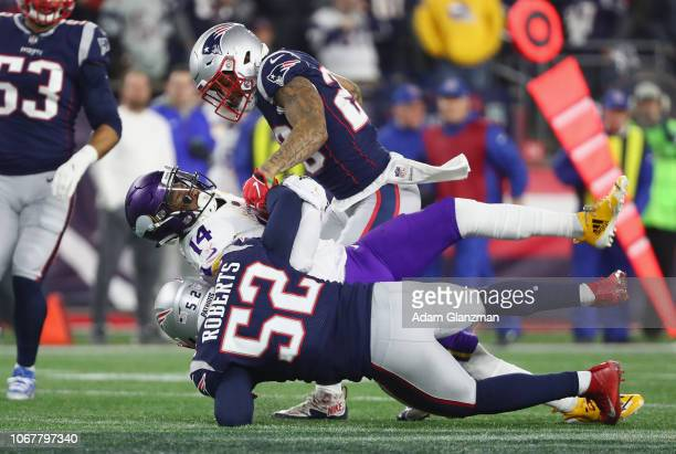 Stefon Diggs of the Minnesota Vikings is tackled by Patrick Chung and Elandon Roberts of the New England Patriots during the first half at Gillette...