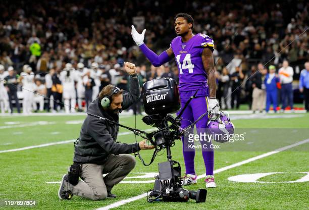 Stefon Diggs of the Minnesota Vikings reacts as a technician works to repair a Skycam on the field after a malfunction during the first half of the...