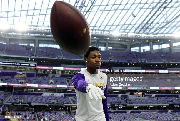 Stefon Diggs of the Minnesota Vikings throws a football with fans before a game against the Denver Broncos at US Bank Stadium on November 17 2019 in...