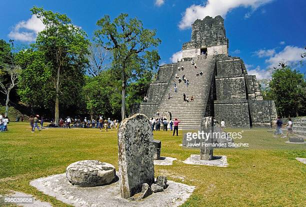 stelae, altars and temple ii or temple of the masks located in the great square of the maya city of tikal, surrounded by numerous national and international tourists, who enjoy the greatness of this important enclave of mayan culture. - merida mexico stock photos and pictures