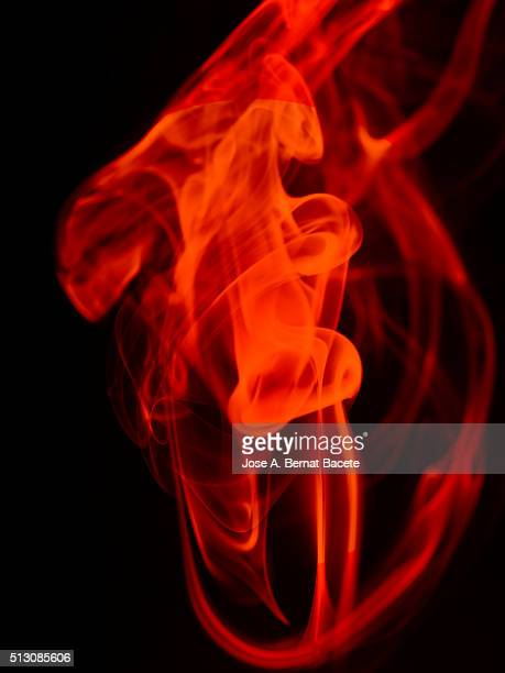 Stelas and figures of orange smoke on a  black blackground.