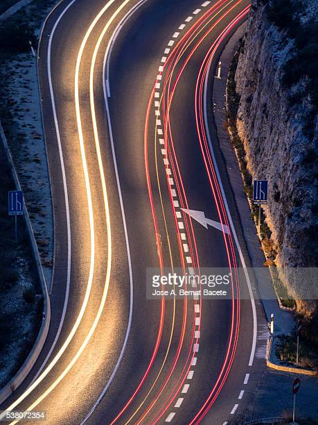 Stelas of lights of cars in a curve of road in the shape of s during the night