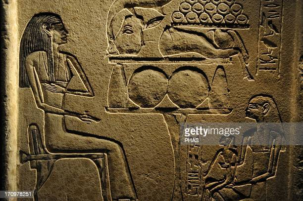 Stele of Itenhab who is seated at an offering table Opposite her is her son with an older woman probably the son's nurse Limestone Middle Kingdom...