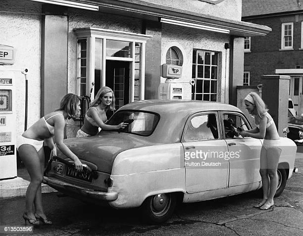 Stella Long Marilyn Woolhead and Karen Lewis help promote European Petroleum clad in their bikinis at a petrol station in Ealing 1965