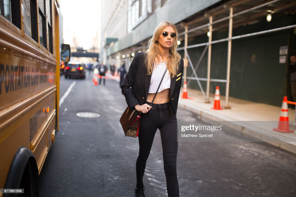 Stella Maxwell is seen on the street attending Zadig & Voltaire during New York Fashion Week wearing a military blazer with white crop top and black pants on February 12, 2018 in New York City.