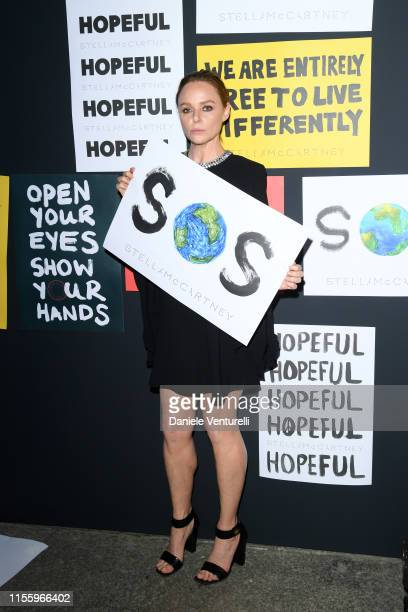 Stella McCartney poses with a sign readin 'SOS' during the presentation of Stella McCartney during the Milan Men's Fashion Week Spring/Summer 2020 on...