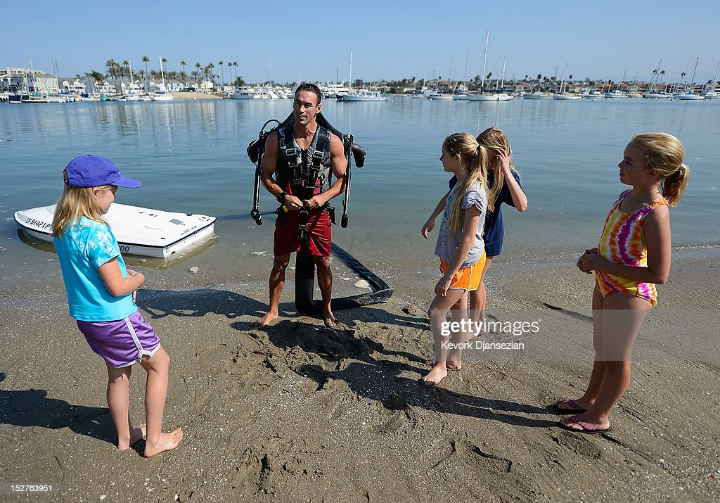 Stella Robson, 9, (L) her sister Hanna Robson, 11, (R) twins sisters Ani Burns, 10 (C) and Jennifer Burns (2nd R) look on as Dean O'Malley demonstrates a JetLev, a water-powered Jetpack flying machine in the Newport Beach harbor on September 25, 2012 in Newport Beach, California. O'Malley will attempt to establish a new world record for flight of the JeLev by making a 26 mile open ocean crossing from Newport Beach to Avalon, Catalina Island on September, 29, 2012.