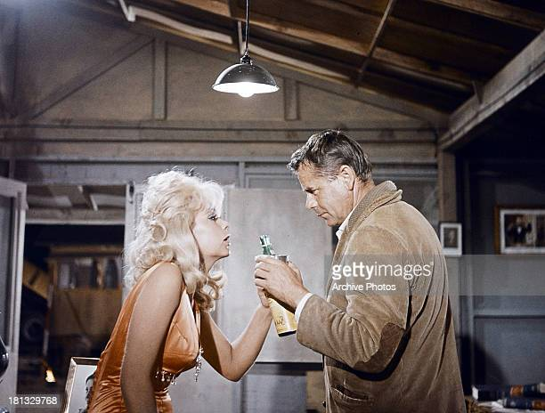 Stella Stevens grabs a bottle from Glenn Ford in a scene from the film 'Rage' 1966