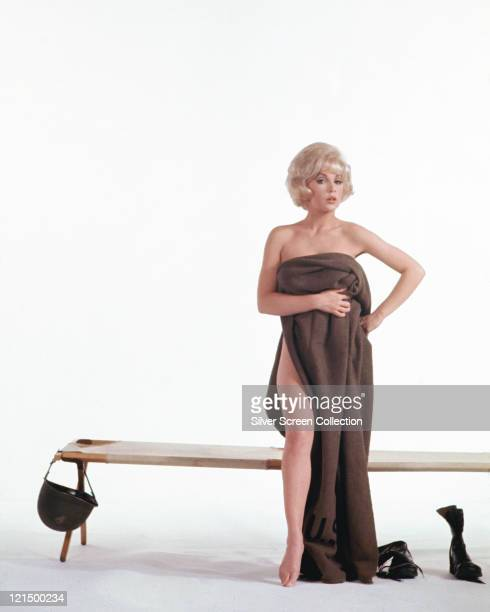 Stella Stevens US actress poses naked but for a brown towel wrapped around her beside a low bench from which a soldier's helmet hangs in a studio...