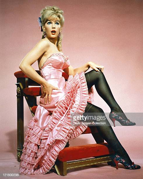 Stella Stevens US actress wearing a strapless long pink burlesque dress with a pink ruffle skirt posing on a set of library step in a studio portrait...