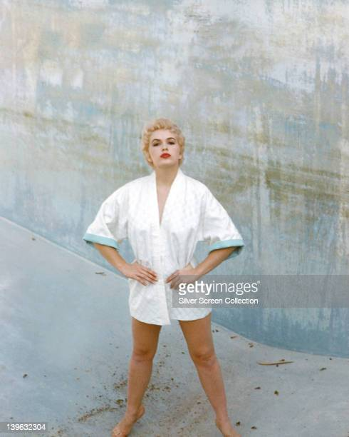 Stella Stevens US actress wearing a white dressing gown as she poses defiantly standing at the bottom of an empty swimming pool circa 1960