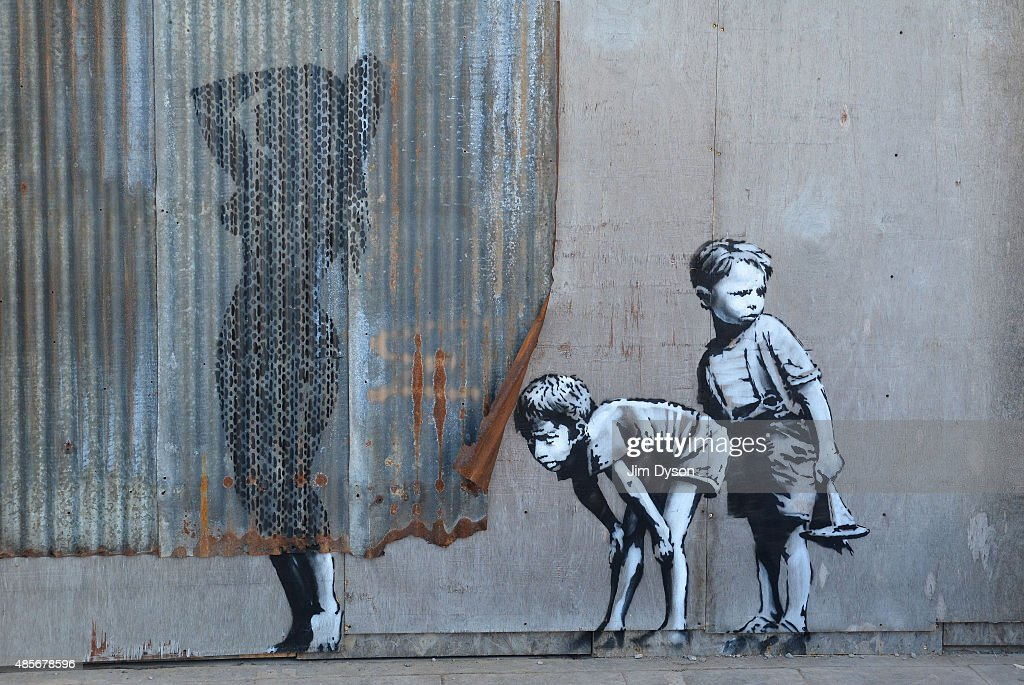 A stencil mural by Banksy depicting boys spying on a woman having a shower, as Banksy's Dismaland Bemusement Park opens to the public, on August 28, 2015 in Weston-Super-Mare, England. Graffiti artist Banksy has opened the subversive, pop-up theme park styled exhibition at the derelict seafront Tropicana lido, featuring the work of 50 artists. The 'Bemusement Park' combines dark humour and 'entry-level anarchism' and will open for just five weeks.