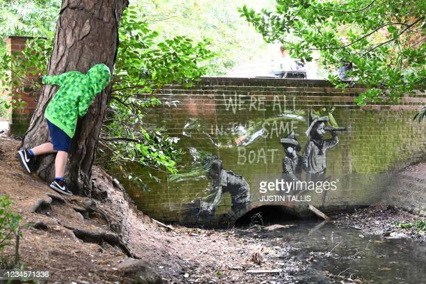 Stensil of children playing at being sailors is the subject of a graffiti artwork bearing the hallmarks of street artist Banksy on the wall of a...