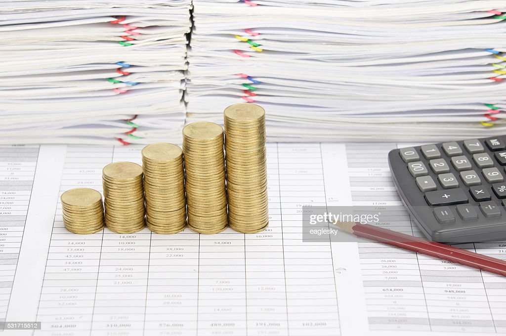 Step Pile Of Gold Coins With Pencil And Calculator Stock Photo