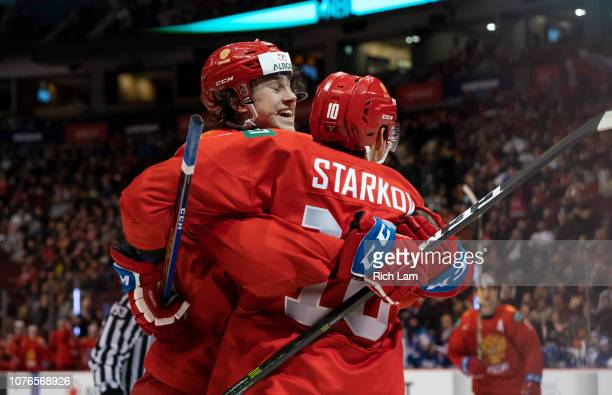 Stepan Starkov of Russia celebrates with teammate Alexander Romanov after scoring a goal against Slovakia in Quarterfinal hockey action of the 2019...