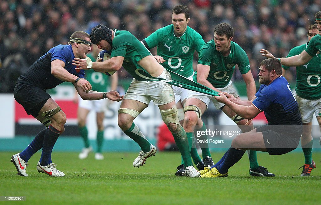 Stepen Ferris of Ireland is held by Vincent Debarty during the RBS Six Nations match between France and Ireland at Stade de France on March 4, 2012 in Paris, France.