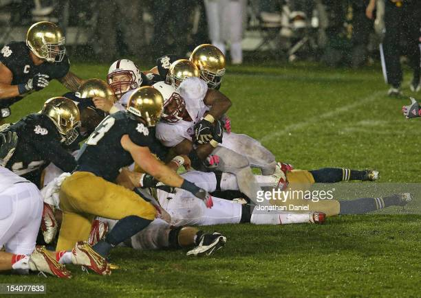Stepfan Taylor of the Stanford Cardinal is stopped short of the goal by members of the Notre Dame Fighting Irish defense on the last play of the game...