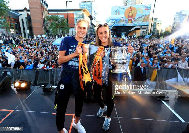 Steph Houghton and Georgia Stanway of Manchester City celebrate with the FA Women's League Cup trophy and the The SSE Women's FA Cup trophy during...