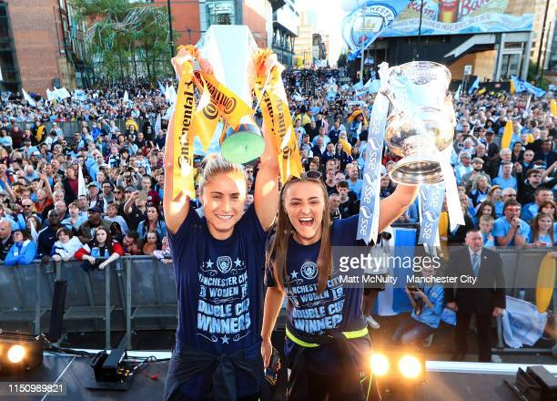 Steph Houghton and Georgia Stanway of Manchester City celebrate with the Women's FA Cup and Continental Cup trophies during the Manchester City Teams...