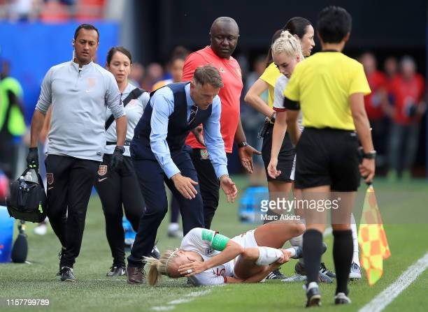 Steph Houghton of England reacts after she is fouled infront of Philip Neville Head Coach of England and Alain Djeumfa Head Coach of Cameroon during...