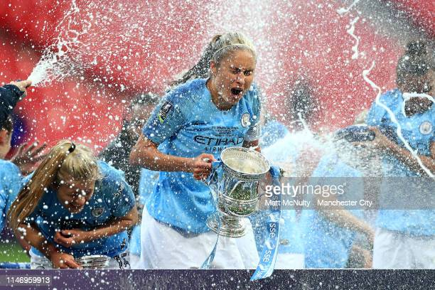 Steph Houghton of Manchester City Women is sprayed with champagne as she celebrates with the Women's FA Cup Trophy following her team's victory in...