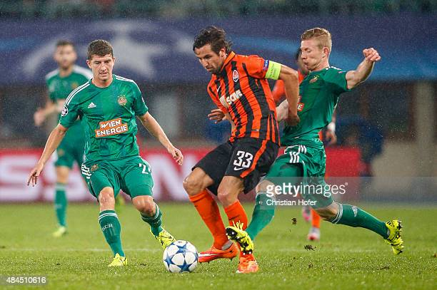 Stephan Auer and Florian Kainz of Vienna compete for the ball with Darijo Srna of Donetsk during the UEFA Champions League Qualifying Round Play Off...