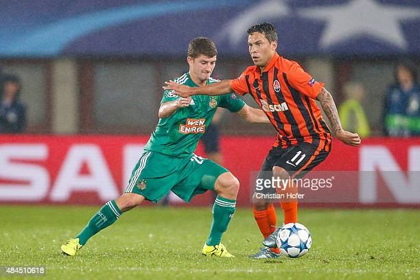 Stephan Auer of Vienna competes for the ball with Marlos of Donetsk during the UEFA Champions League Qualifying Round Play Off First Leg match...