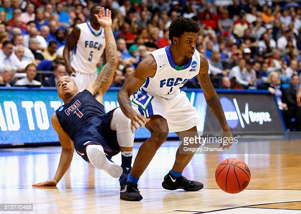 Stephan Jiggetts of the Fairleigh Dickinson Knights falls as Reggie Reid of the Florida Gulf Coast Eagles handles the ball in the second half of...