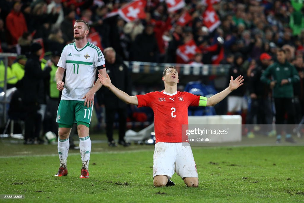 Stephan Lichsteiner of Switzerland celebrates the qualification for Russia while Chris Brunt of Northern Ireland looks down at final whistle of the FIFA 2018 World Cup Qualifier Play-Off: Second Leg between Switzerland and Northern Ireland at St. Jakob-Park stadium on November 12, 2017 in Basel, Basel-Stadt, Switzerland.