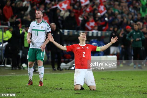 Stephan Lichsteiner of Switzerland celebrates the qualification for Russia while Chris Brunt of Northern Ireland looks down at final whistle of the...