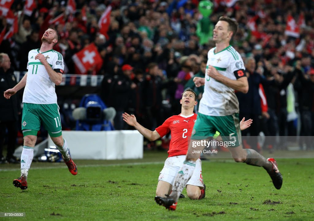 Stephan Lichsteiner of Switzerland celebrates the qualification for Russia while Chris Brunt and Jonny Evans of Northern Ireland look dejected at final whistle of the FIFA 2018 World Cup Qualifier Play-Off: Second Leg between Switzerland and Northern Ireland at St. Jakob-Park stadium on November 12, 2017 in Basel, Basel-Stadt, Switzerland.