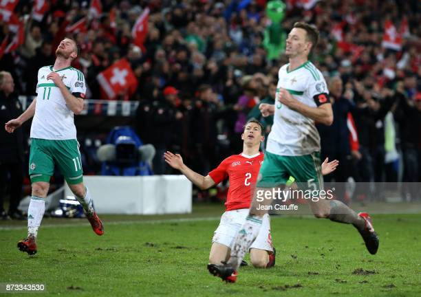 Stephan Lichsteiner of Switzerland celebrates the qualification for Russia while Chris Brunt and Jonny Evans of Northern Ireland look dejected at...