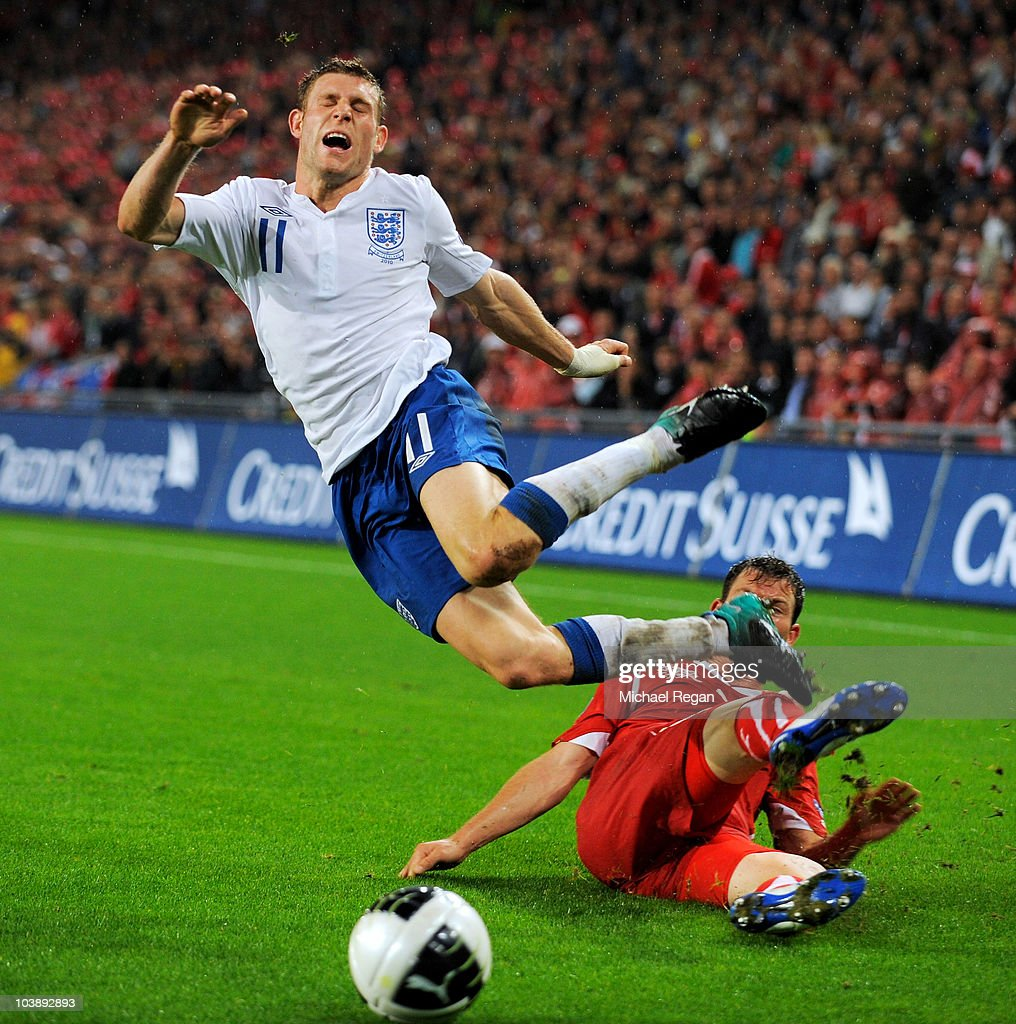 Stephan Lichsteiner of Switzerland fouls James Milner of England and receives a red card for a second bookable offence during the EURO 2012 Group G Qualifier between Switzerland and England at St Jakob Park on September 7, 2010 in Basel, Switzerland.