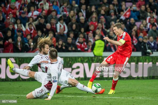 Stephan Lichsteiner shoots against Kaspars Gorkss and Vitalijs Jagodinskis during the World Cup Qualifiers group match between Switzerland and Latvia...
