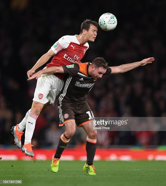 Stephan Lichtsteiner of Arsenal heads the ball under pressure Alan Judge of Brentford during the Carabao Cup Third Round match between Arsenal and...