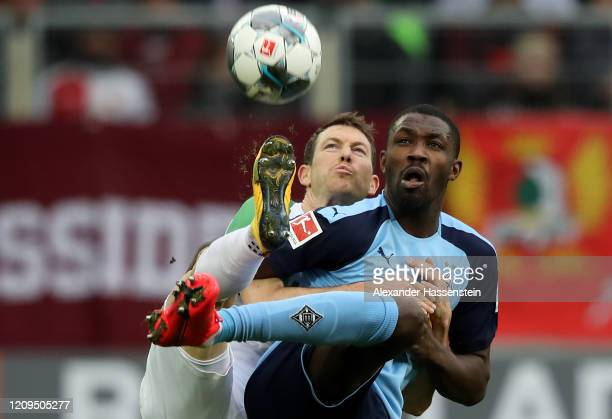 Stephan Lichtsteiner of Augsburg and Marcus Thuram of Borussia Monchengladbach battle for possession during the Bundesliga match between FC Augsburg...