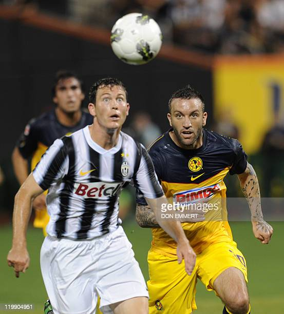 Stephan Lichtsteiner of Juventus and Matias Vuoso of Club America go after the ball during the Herbalife World Football Challenge match between Club...