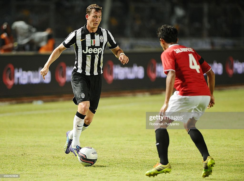 Stephan Lichtsteiner (L) of Juventus FC runs with ball during the pre-season friendly match between Indonesia Selection All Star Team and Juventus FC at Gelora Bung Karno Stadium on August 6, 2014 in Jakarta, Indonesia. Juventus FC won the game 8-1.