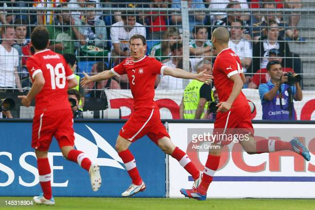 Stephan Lichtsteiner of Switzerland celebrates his team's fourth goal with team mates Eren Derdiyok and Admir Mehmedi during the international...