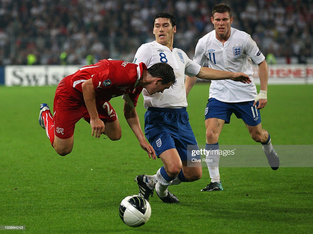 Stephan Lichtsteiner of Switzerland is tackled by Gareth Barry of England during the EURO 2012 Group G Qualifier between Switzerland and England at St Jakob Park on September 7, 2010 in Basel, Switzerland.