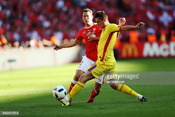 Stephan Lichtsteiner of Switzerland vies with Steliano Filip of Romania during the UEFA EURO 2016 Group A match between Romania and Switzerland at...