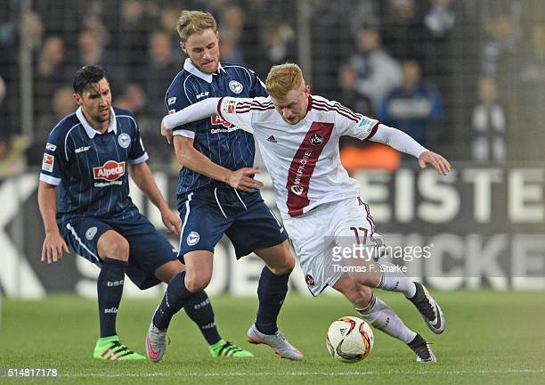 Stephan Salger and Felix Burmeister of Bielefeld fight for the ball with Sebastian Kerk of Nuernberg during the Second Bundesliga match between...