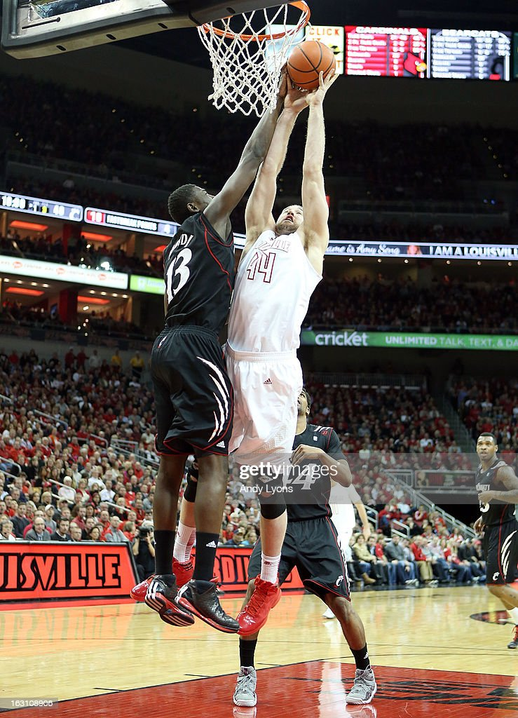 Stephan Van Treese #44 of the Louisville Cardinals and Cheikh Mbodj #13 of the Cincinnati Bearcats reach for a rebound during the game at KFC YUM! Center on March 4, 2013 in Louisville, Kentucky.