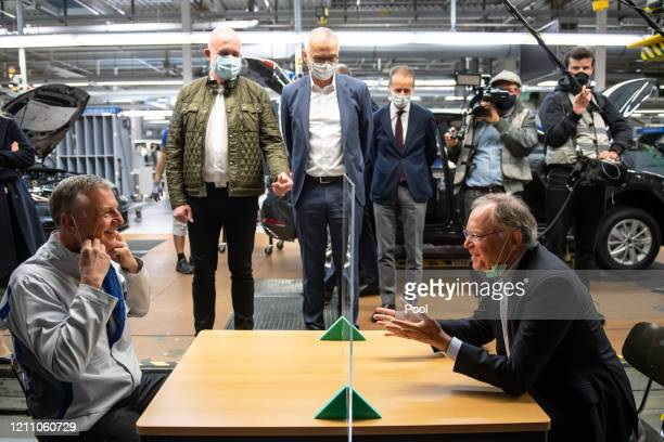 Stephan Weil , Prime Minister of Lower Saxony, and Stefan Loth, the plant manager, sit at a table in production that is divided with a plexiglass...