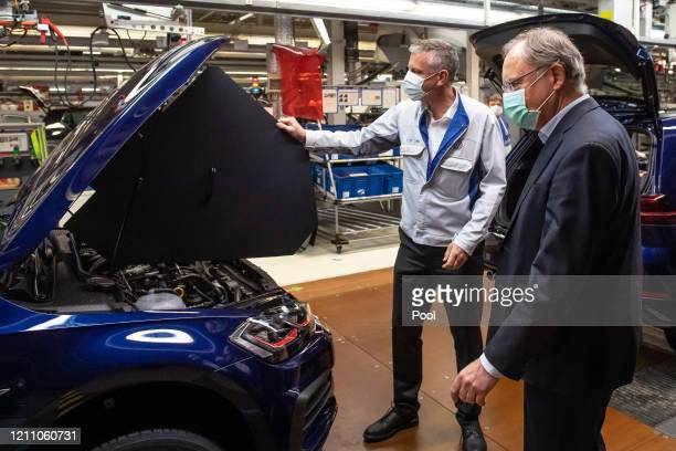 Stephan Weil , Prime Minister of Lower Saxony, and Stefan Loth wear face masks during a visit to the production line at the Wolfsburg Plant....